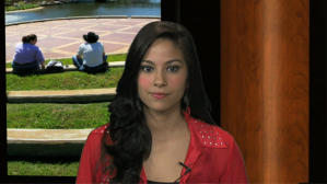 Shot of Alexis Locklear as a news desk anchor in the TV studio