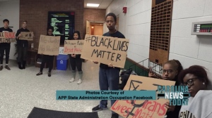Students stand with posters in hallway, including Black Lives Matter poster