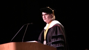 Margaret Spellings wearing academic regalia and speaking at podium