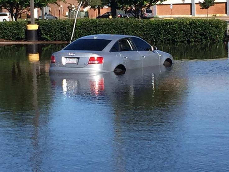 car partially submerged in campus parking lot